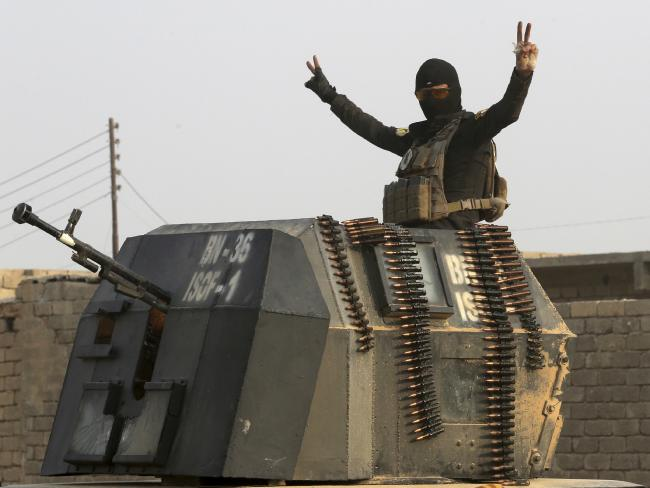 A member of Iraq's elite counter-terrorism forces in a military convoy flashes a victory sign as forces advance toward Islamic State positions in the village of Tob Zawa, about 9 kilometres from Mosul, Iraq. Picture: AP