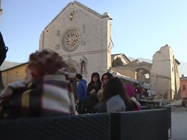 Residents who fled from their houses gather in a square in front of a damaged church in Norcia, Italy. Picture: Sky Italia via AP
