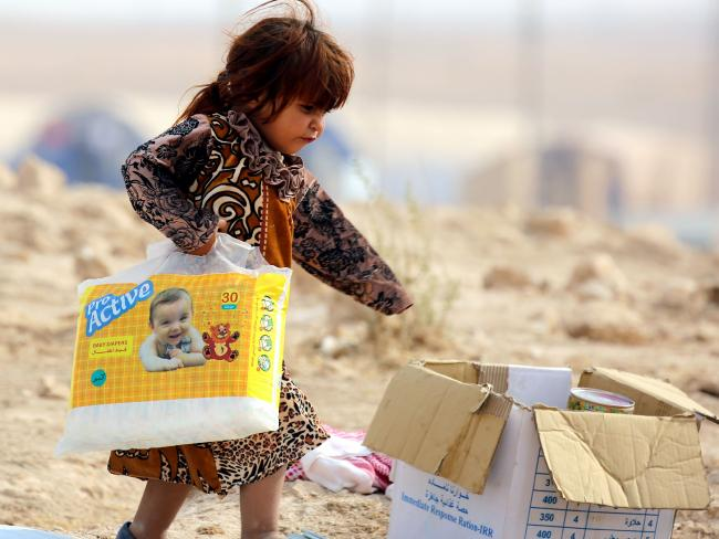 An Iraqi refugee who fled Mosul, the last major Iraqi city under the control of the Islamic State (IS) group, due to the Iraqi government forces offensive to retake the city, carries diapers at the UN-run Al-Hol refugee camp in Syria's Hasakeh province. Picture: AFP