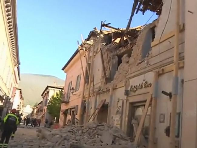 Firefighters stand in front of a damaged building in Norcia. Picture: Sky Italia via AP