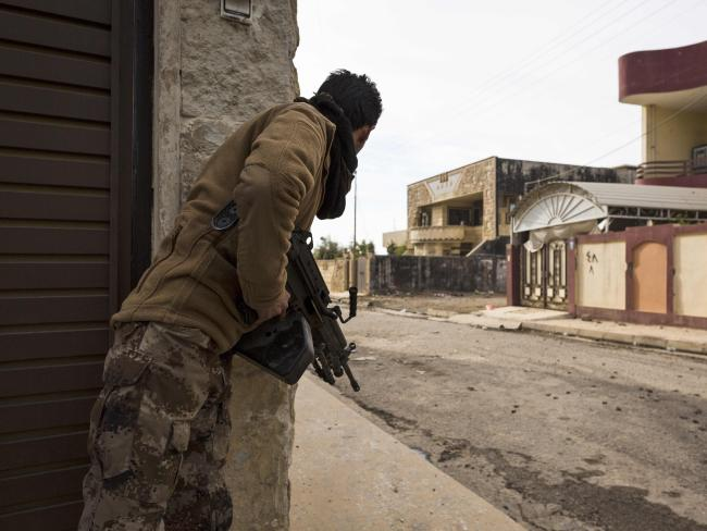 A soldier from the Mosul Brigade of the Iraqi Special Operations Force 2 (ISOF 2) tries to spot enemy positions held by jihadists of the Islamic State (IS) group. Picture: AFP