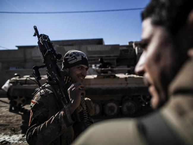 An Iraqi soldier from the 9th Infantry Division holds his machine gun while heading to the frontline in Shyma district in Mosul, Iraq, Tuesday. Picture: AP