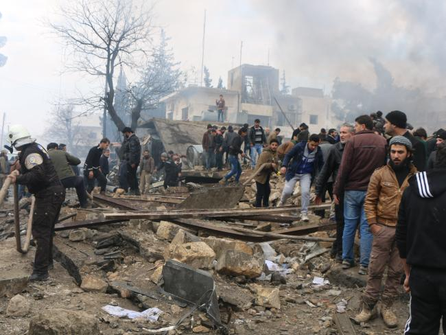 Rescue workers attend to the wreckage after dozens were killed by a car bomb in Azaz. Picture: AP