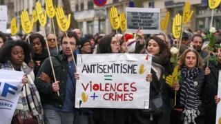 Demonstrators hold signs against anti-Semitism during a silent march in Paris on March 28, 2018, in memory of Mireille Knoll