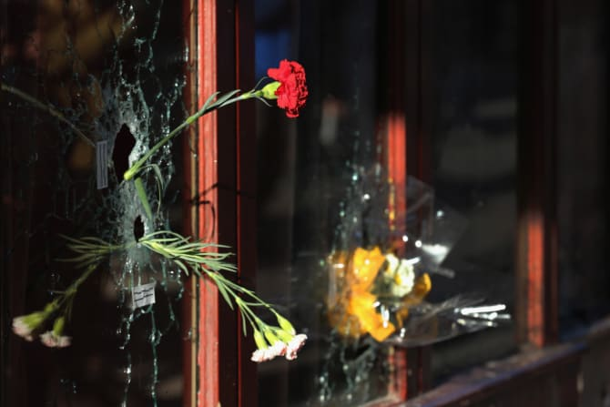 Flowers inside bullet holes in the window of Le Carillon restaurant, where the Paris terrorist attacks of November 2015, began to unfold.